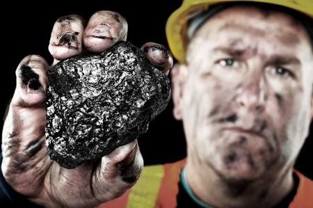carbone: Un minatore sporco mostra un pezzo di carbone come fonte di energia e di potenza. Archivio Fotografico