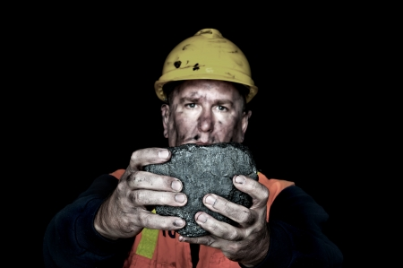 COAL MINER: A coalminer holds out a large chunk of energy rich coal in a dark coalmine. Stock Photo