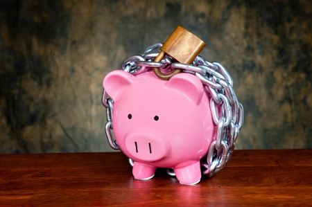 bank protection: A pink piggybank chained up and locked. Image can be used for financial protection inferences or other investment messages.
