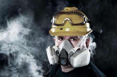 Un travailleur de sauvetage porte un masque dans un smokey, atmosphère toxique. Image montre l'importance de la préparation de protection et de sécurité.