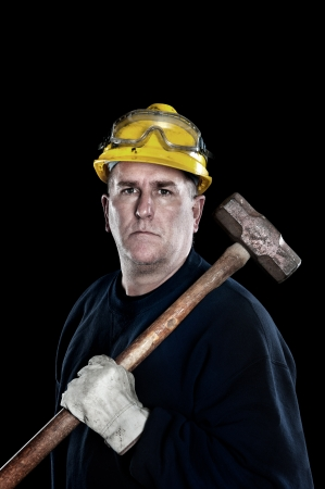 protective: A manual laborer with a sledgehammer wearing a yellow hardhat and protyective work gloves isolated on black Stock Photo