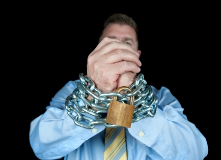 A businessman has his hands chained up to insinuate that he needs to be controlled.