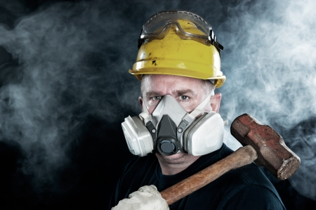 respiratory apparatus: A rescue worker wears a respirator in a smokey, toxic atmosphere carrying a sledgehammer.