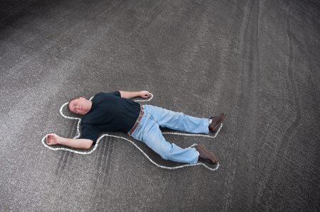 skid marks: A man dead in the street outlined with chalk by crime scene investigators.