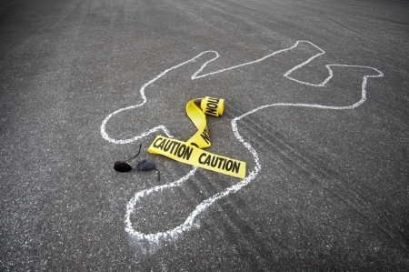 scene of a crime: Caution tape and broken sun glasses rest near a chalk line from an auto accident.