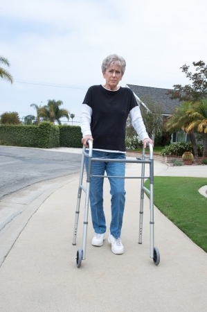 An elderly woman uses a walker to assist her balance while walking on the sidewalk.