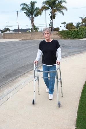 An elderly woman uses a walker to assist her balance while walking on the sidewalk. photo