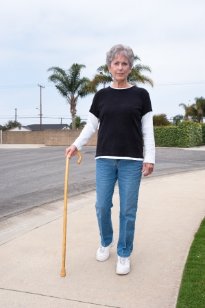 A woman uses a wooden cane to assist her while walking down a sidewalk. photo