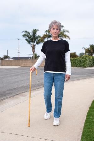 Een vrouw maakt gebruik van een houten stok om haar te helpen tijdens het lopen onderaan een stoep.