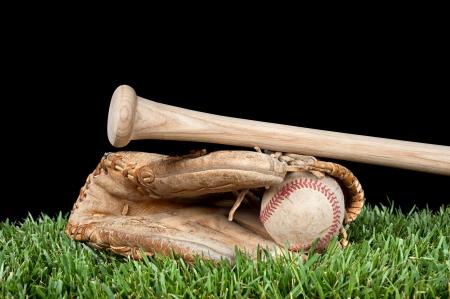 guante de beisbol: Guante de béisbol, pelota y bate por la que se en la hierba con un fondo negro para la colocación de la copia. Foto de archivo