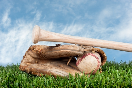 placement: Baseball glove, ball, and bat laying on grass against a blye, lightly cloudy sky for placement of copy.