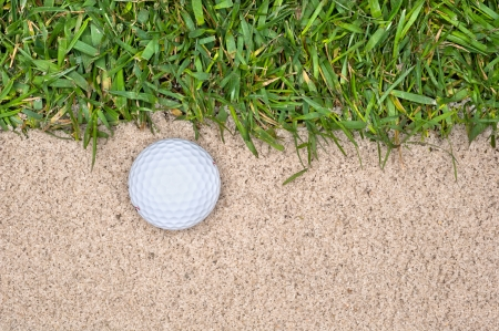 A golf ball in a sand trap next to the rough highlights the mistakes one can make playing the game. photo