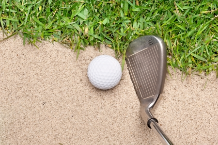 A golf ball in a sand trap getting ready to be hit with an iron. photo