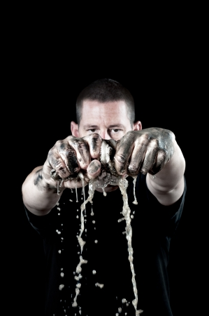 A man wrings out a diry water soaked rag with grungy, filthy hands. Focus is on the hands and rag. photo