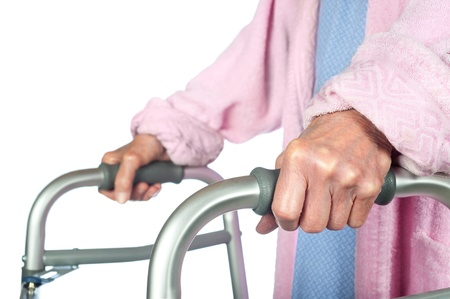 An elderly senior adult using a walker to help her mobility.  Focus is on the hand. photo