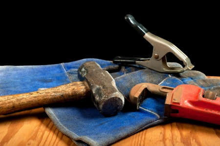 Grungy, old tools including a clamp, sledgehammer and pipe wrench with blue leather gloves. photo