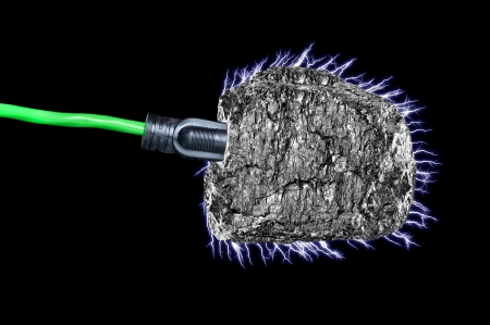 bituminous coal: A conceptual image of an extension cord plugged intop a chunk of bituminous coal with electrical current flowing.  Stock Photo