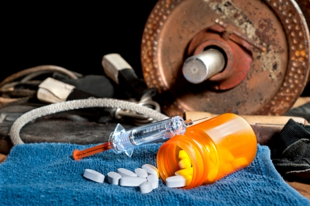 inferences: Steroid medication including pills and a syringe in front of exercise equipment.  Image can be used for steroid and performancing enhancement inferences in sports.