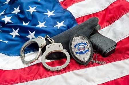 security laws: Police badge, gun and handcuffs on an American flag symbolizing law enforcement in the United States. Stock Photo