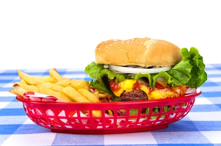 A freshly grilled cheeseburger in a red basket with freshly cooked french fries. Stock Photo