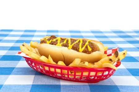 picnic tablecloth: Side view of a chilidog with french fries on a checkered tablecloth.  Image was set up so designers can drop in any background they wish.