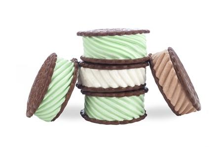 Een verzameling van chocolade, vanille en mint ijs sandwiches op een witte achtergrond.