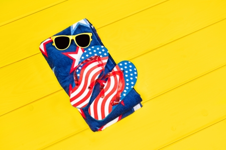 Fourth of July flip flops and patriotic towel resting on a yellow pool deck.  Plenty of room for copy. Stock Photo - 14820736