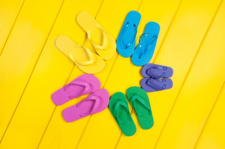 An assortment of colorful rubber flip flops in a circular pattern on a wooden, yellow pool deck. photo