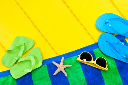 beach towel: A beach towel, flip flops and sunglasses on a colorful yellow wooden deck with the presence of a starfish to insinuate a beach relates setting