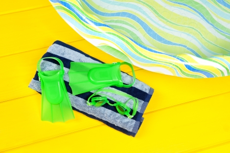 Swim flippers and eye goggles on a beach towel next to a plastic youth swimming pool  Stock Photo - 14815808
