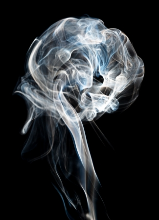 nebulous: A plume of backlit cigeratte smoke against a black background  Stock Photo