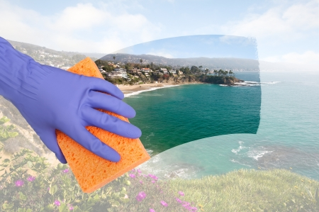 window cleaning: A maid cleaning windows on a cliff side home overlooking a cove along the ocean