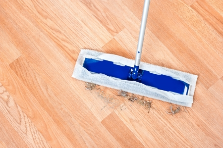 Image of a modern floor dusting mop being used to clean hair and dirt on a wooden laminent floor  photo
