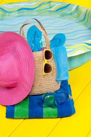 A straw beach bag full of accessories rests on a beach towel next to a children Stock Photo - 14826934