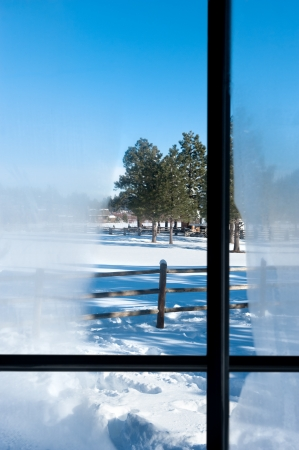 A view out a cabin window with condensation overlooking a snowy mountain landscape