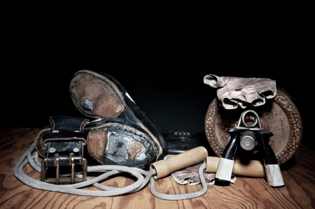run down: A set of used, run down exercise equipment including hand grips, a jump rope, weightlifting belt, barbell and worn out shoes. Stock Photo
