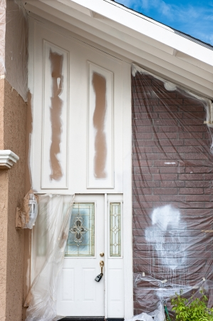 A home repaint project shows the detailed preparation and masking required to do the job properly.  Here is the front walkway of a home that is being repainted with the brick wall being carefully protected with plastic sheeting. photo