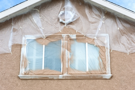A home is being repainted and is painstakenly masked with plastic sheeting to protect areas from paint overspray during a remodeling project. photo