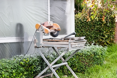 sheeting: A tile saw on the lawn of a home that is being remodeled.  The window is covered with plastic sheeting to protect it from the overspray from the wet saw and also from paint overspray as noted on the top of the shrubbery under the window.