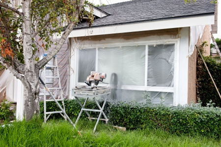 A tile saw and ladder in front of a plastic covered window during a home remodel. photo