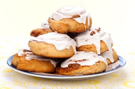 A plate of freshly baked cinnamon rolls with sweet, white icing dripping down the sides. Stockfoto