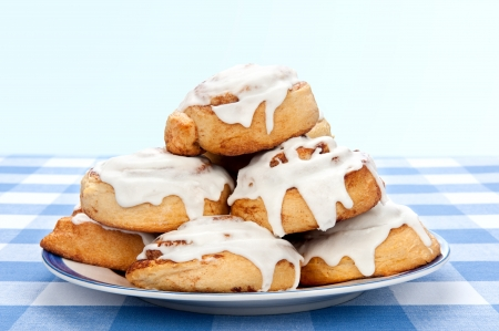 sweet bun: A plate of delicious cinnamon rolls coated with sugary frosting glaze.