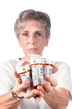 pills in hand: Una mujer adulta mayor muestra los muchos medicamentos que debe tomar para mantenerse saludable.