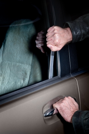 A car thief uses a Slim Jim tool to pop the lock on a car door to steal it. photo