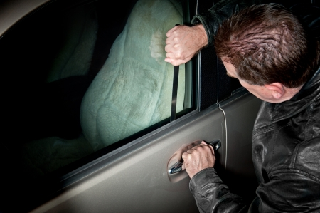 car lock: A male car thief uses a flat metal lock pick to break into a vehicle.