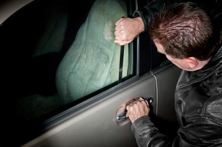 robo de autos: Un ladrón de coches macho utiliza una púa de metal de bloqueo plana para entrar en un vehículo.