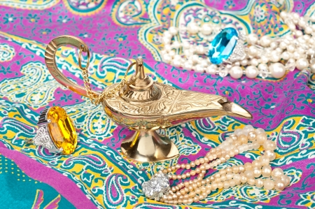antique jewelry: A magic oil lamp on top of gypsy clothing and surrounded by jewelry.
