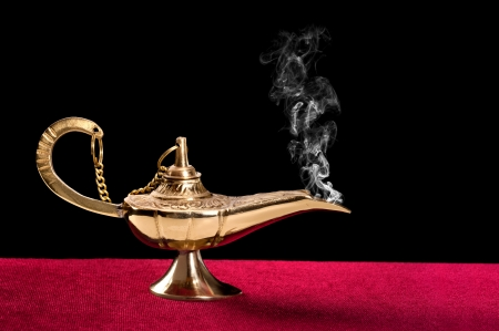 An ancient magic lamp on a red felt table top disperses a stream of mysteus smoke.   Stock Photo - 15519582