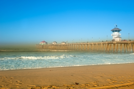 huntington beach: A scenic pier at the beach with smoke from a local fire lining the horizon.