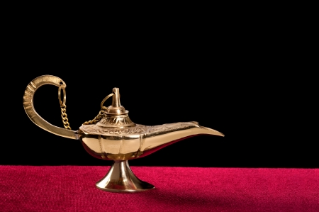A golden genie lamp on red velvet against a black background. Designers have the option to place any kind of smoke or ghostly image coming out of the lamp. Stock Photo - 15519578